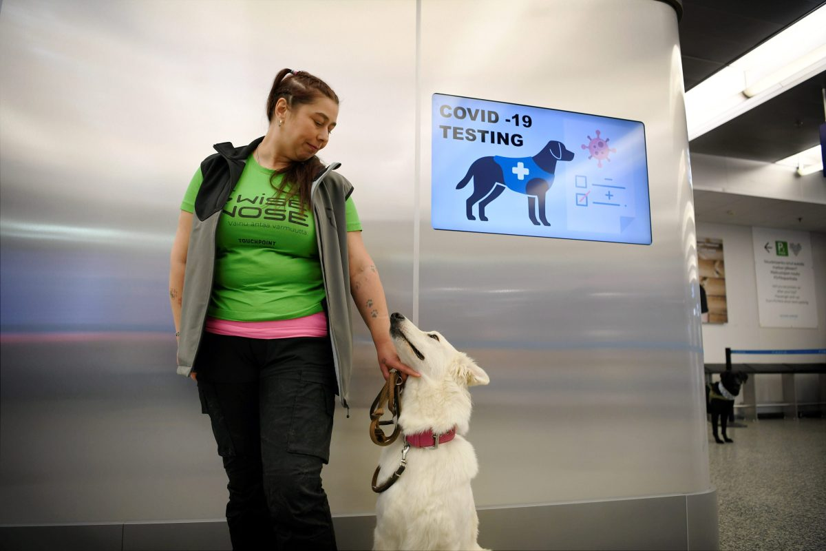 The coronavirus sniffer dog named E.T. receives a cuddle from the trainer Anette Kare at the Helsinki airport in Vantaa, Finland, where he is trained to detect the COVID-19 from the arriving passengers, on September 22, 2020