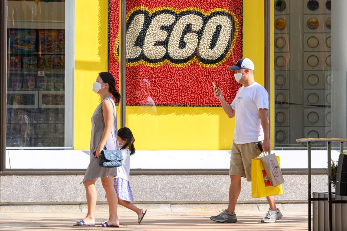 People in masks walk by a Lego storefront