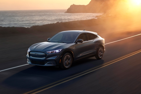 Ford Mustang Mach-E electric crossover SUV driving next to the ocean