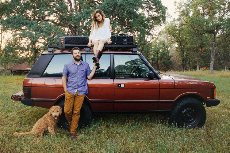 A man, woman and goldendoodle dog next to a red 1991 Range Rover Classic SUV