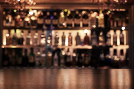 empty wooden bar with booze in the background