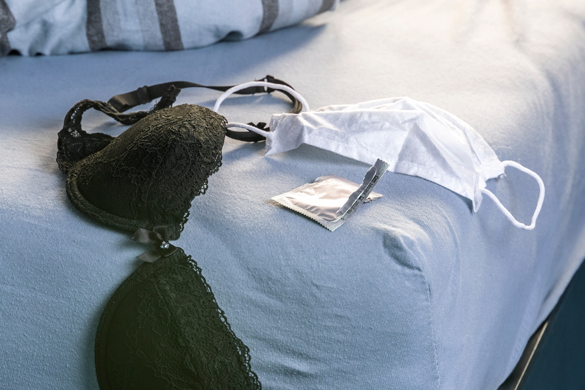a bra, face mask and condom wrapper lying on a bed
