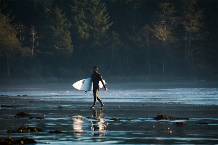 A surfer walking with a surfboard on the beach in Tofino, Canada