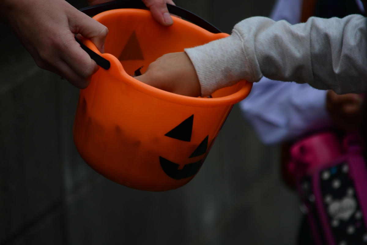 kids trick-or-treating with an orange pumpkin bucket full of candy