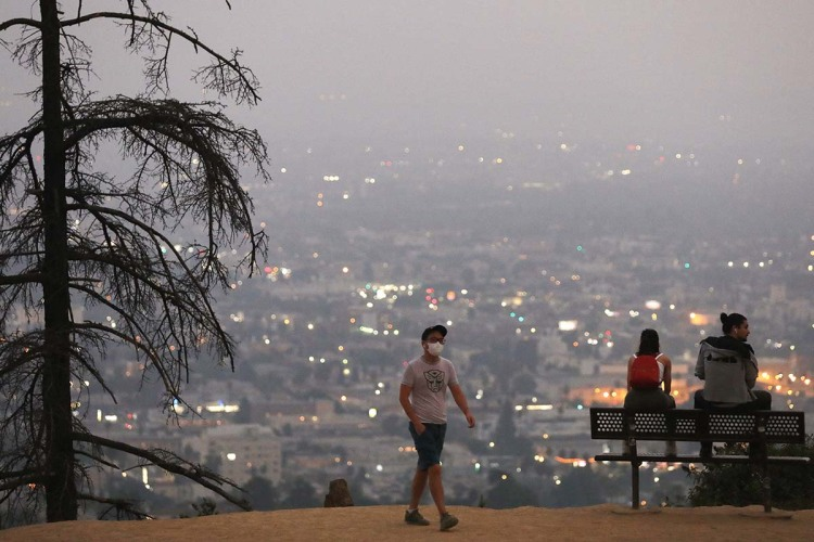 man walking amongst smoke from the wildfires in Los Angeles