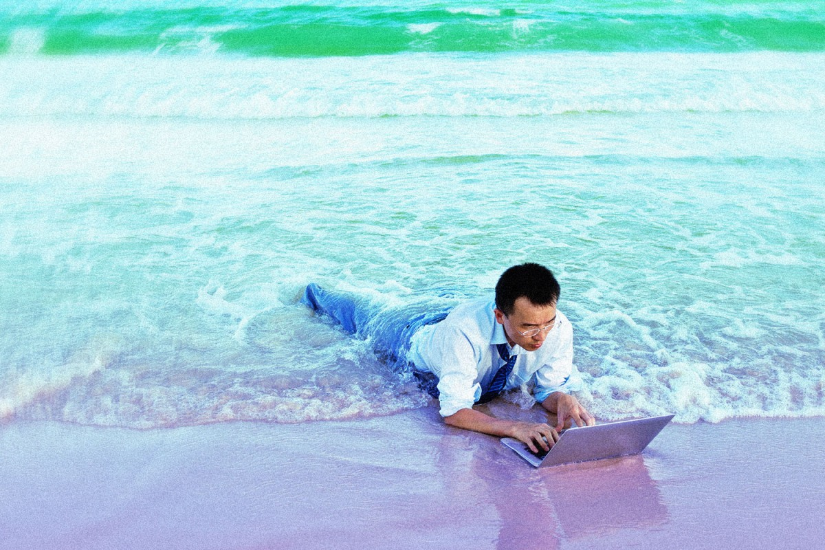 Young businessman on a beach with a laptop.