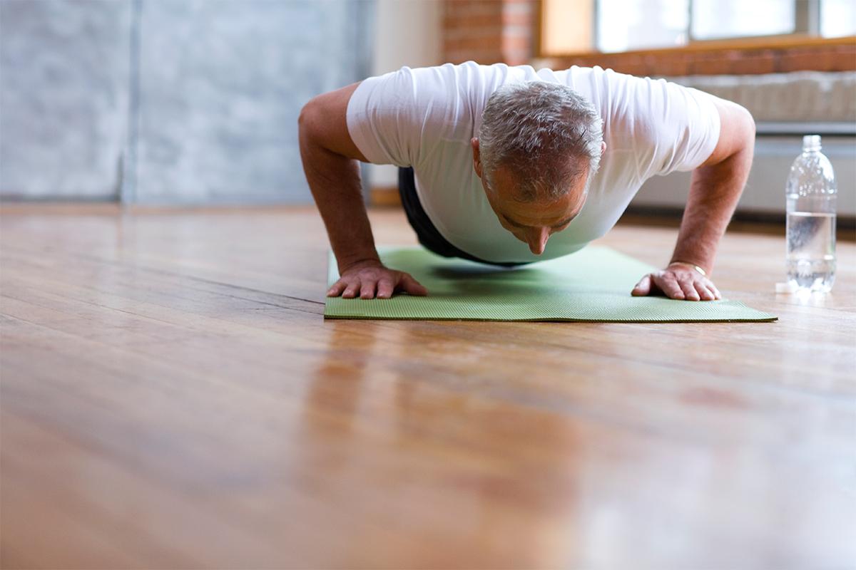 older man doing pushups on a yoga mat