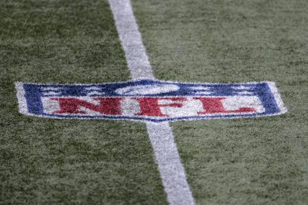NFL logo on the field during a game between the Patriots and Raiders. NFL players have a 73% vaccination rate.