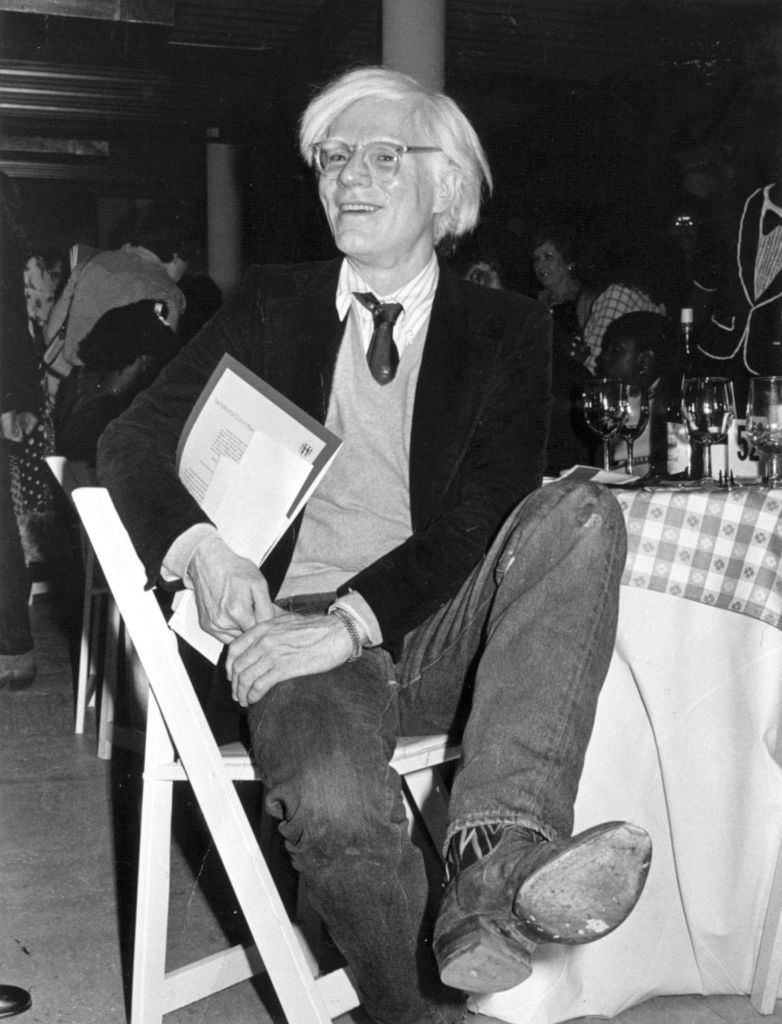 Artist Andy Warhol in cowboy boots at fundraiser, 1979