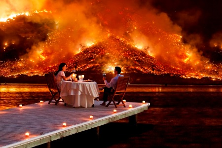couple enjoys a romantic dinner as an apocalyptic hell scape blazes in the distance