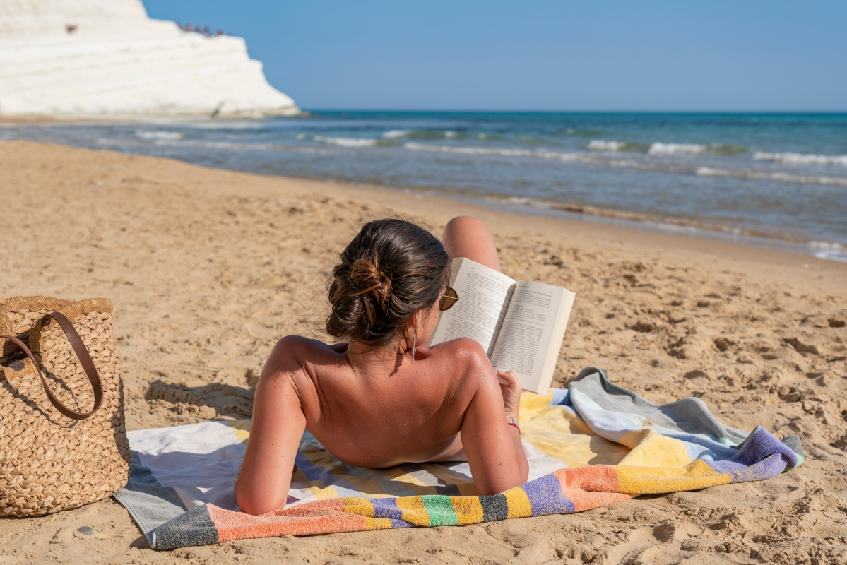 woman reading while sunbathing
