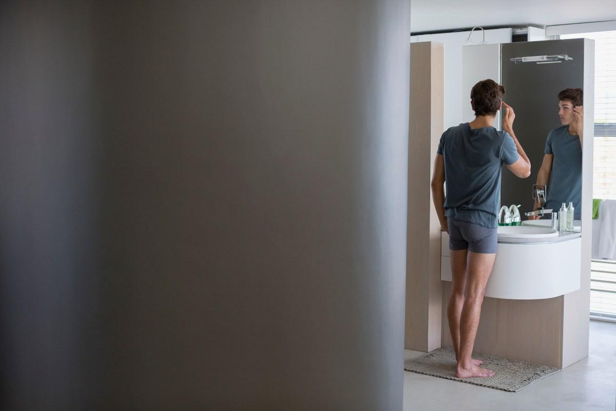 Reflection of a man in bathroom mirror