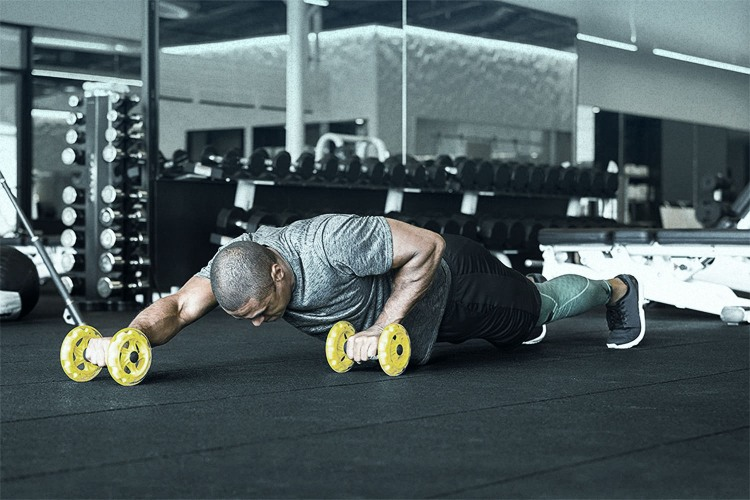 man working out with core wheels
