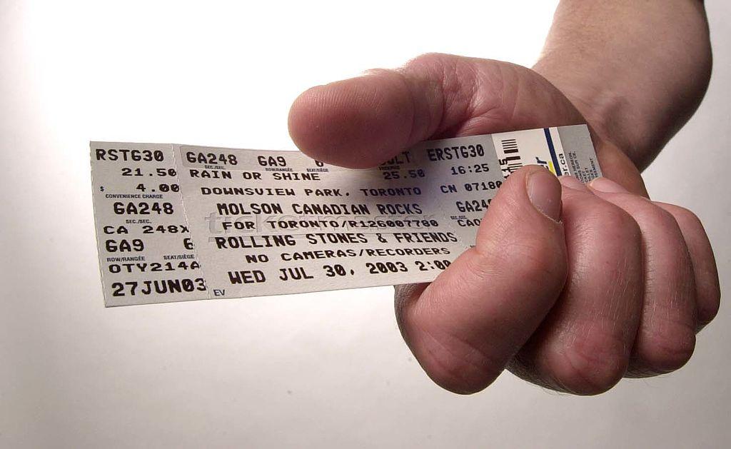 A hand holding a concert ticket