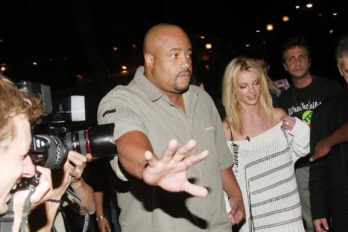 Britney Spears braves a crowd of press photographers in 2003