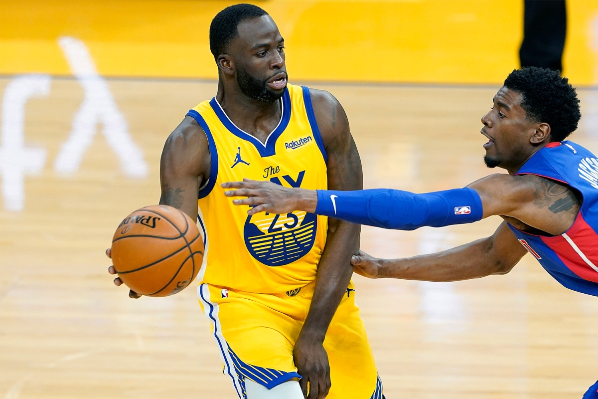 Draymond Green looks to pass the ball while being defended by Josh Jackson.
