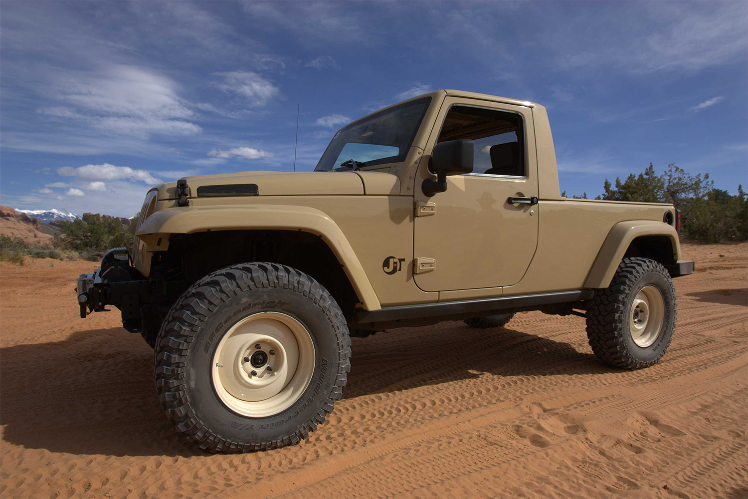 A beige two-door Jeep Wrangler truck in the desert at the Easter Jeep Safari