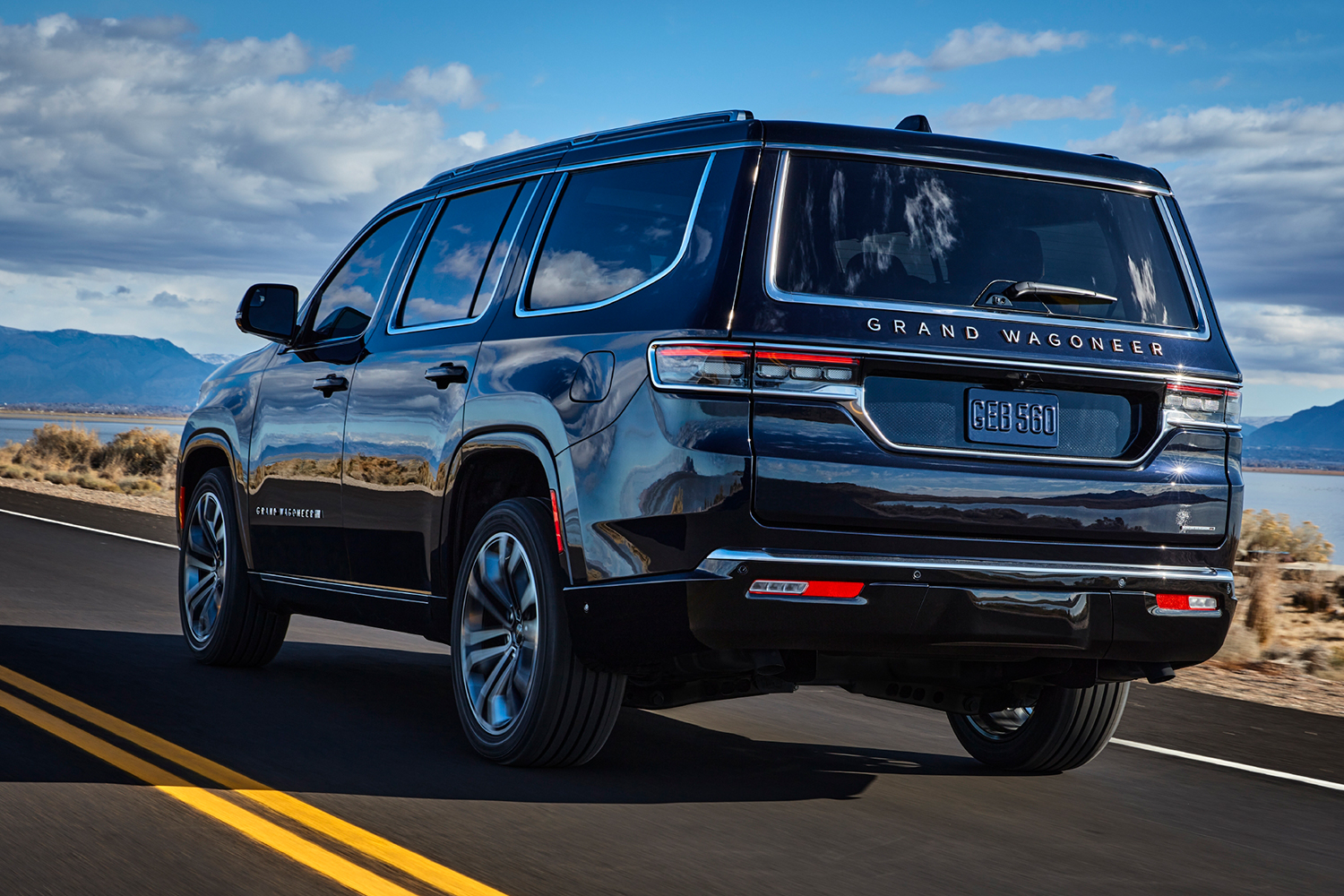 The 2022 Jeep Grand Wagoneer driving down the road shot from the rear left