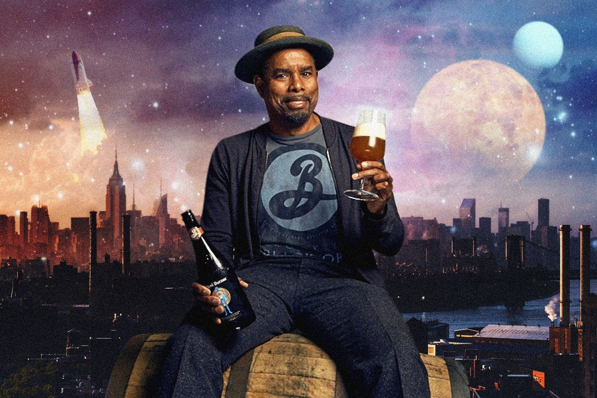 Garrett Oliver of Brooklyn Brewery holds a glass of beer while seated on a cask