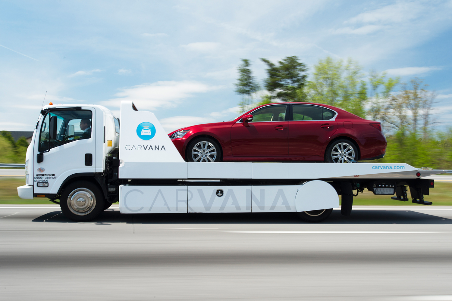 Red car on the back of a Carvana delivery vehicle