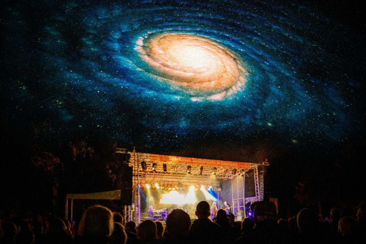 A psychedelic night sky over a music festival