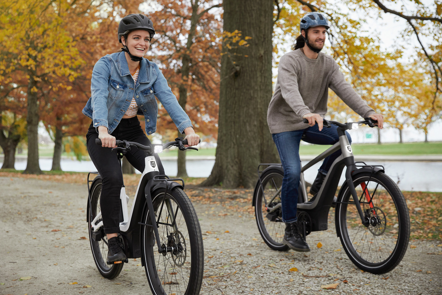 A woman and a man riding two electric bikes from Harley-Davidson's new offshoot company Serial 1 down a street in autumn