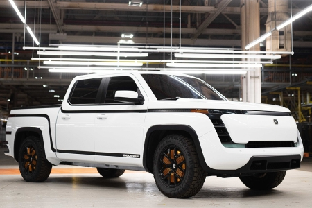 A white electric Endurance pickup truck from Lordstown Motors sitting in a warehouse under lights