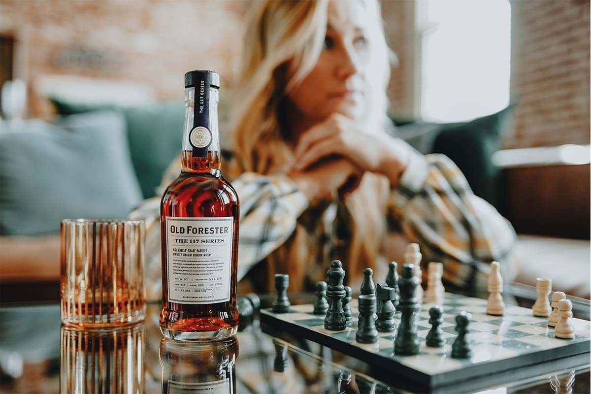 Old Forester Master Taster Jackie Zykan sitting at a table with a chess set and a bottle and glass of Old Forester 117 High Angels' Share