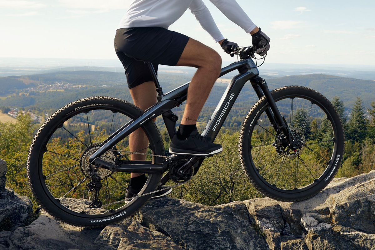 A man on top of a mountain astride the Porsche eBike Cross electric bicycle