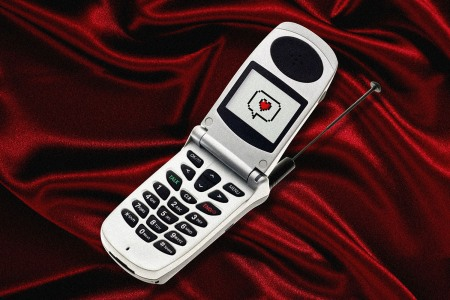 Flip phone on a red velvet background with an 8 bit heart on the screen.