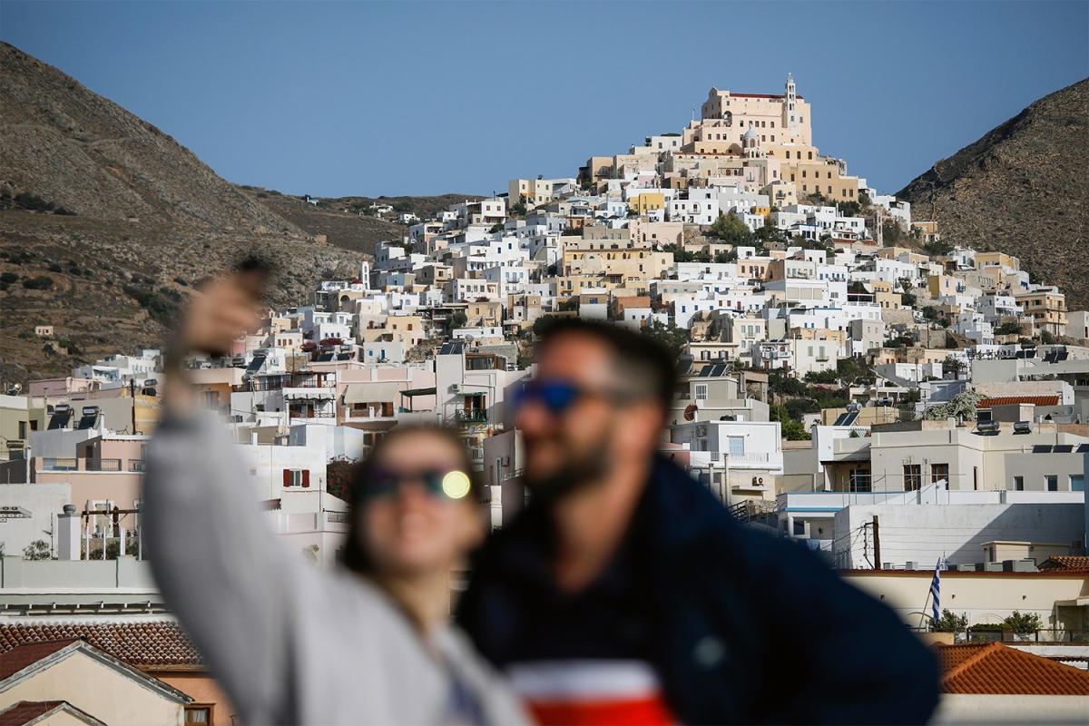 Tourists pose for a selfie in front if Syros Island
