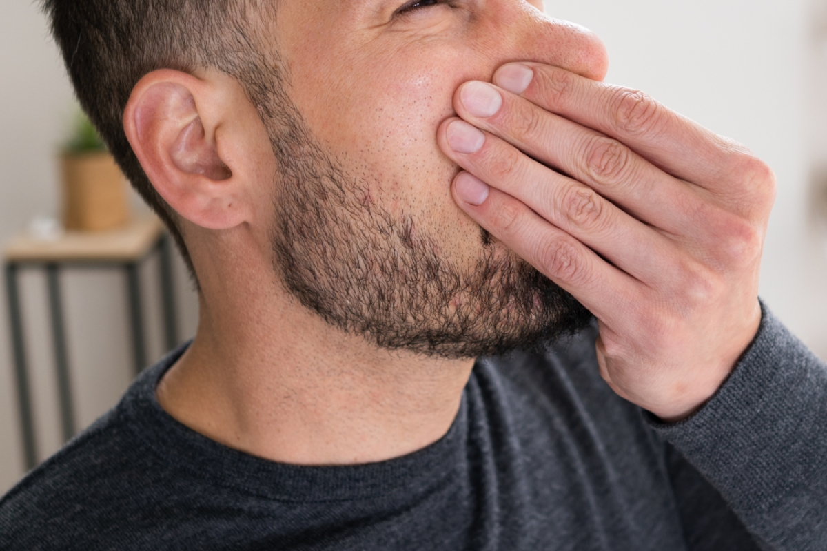close up of a bearded man holding his nose