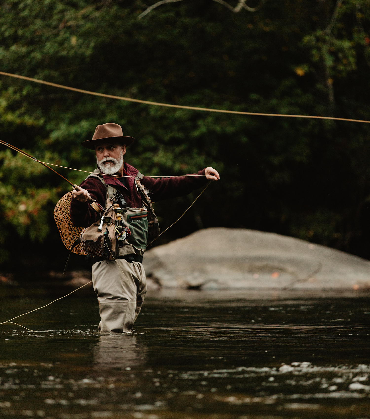 Bamboo fly rod craftsman Bill Oyster fishing in a river with the water up to his knees