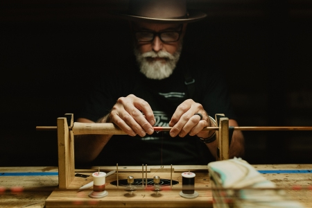 Bill Oyster wrapping a bamboo fly fishing rod on a table