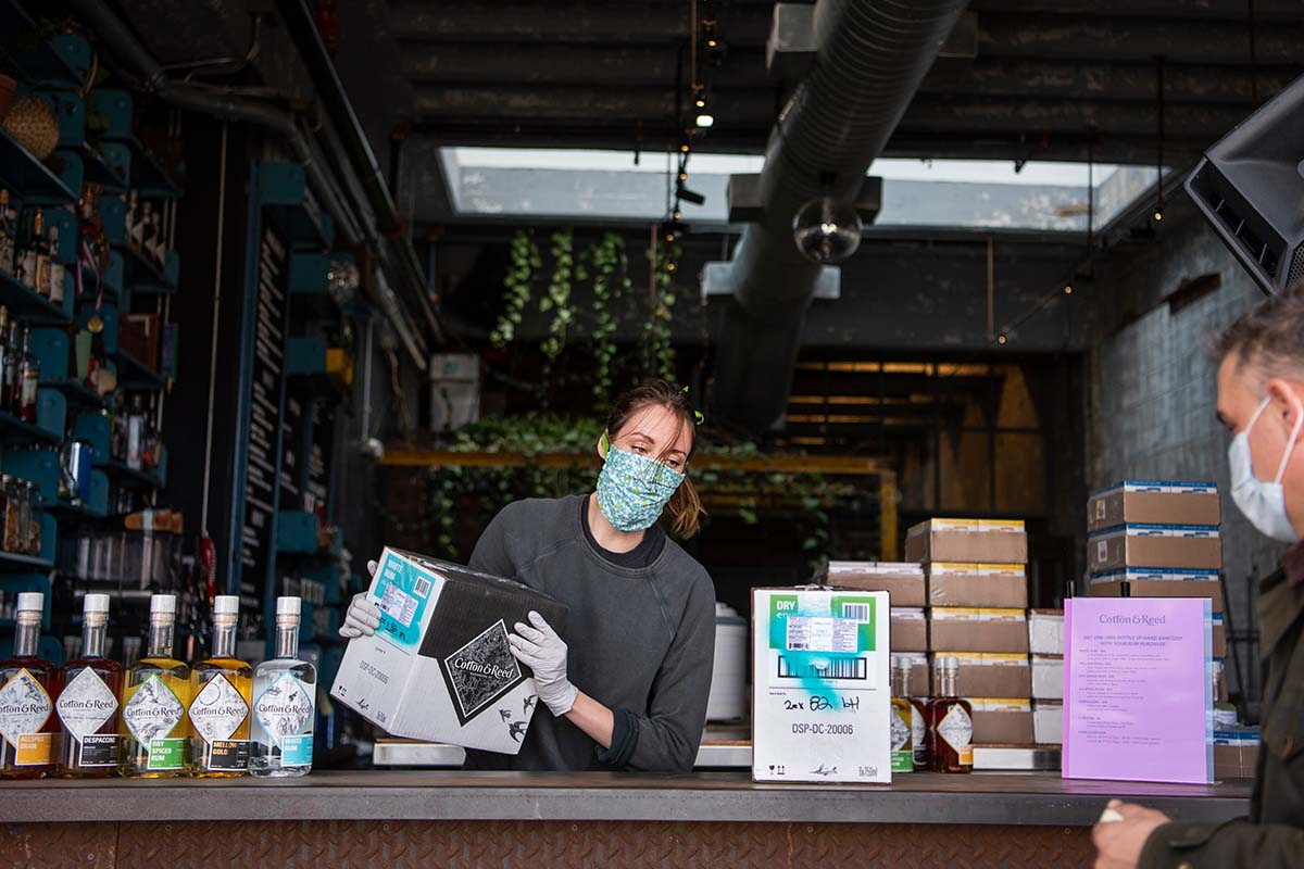 Megan Kyker assists a customer at Cotton & Reed rum distillery in Union Market on Friday, April 3, 2020. Many bars and restaurants are open for takeout orders during the coronavirus outbreak