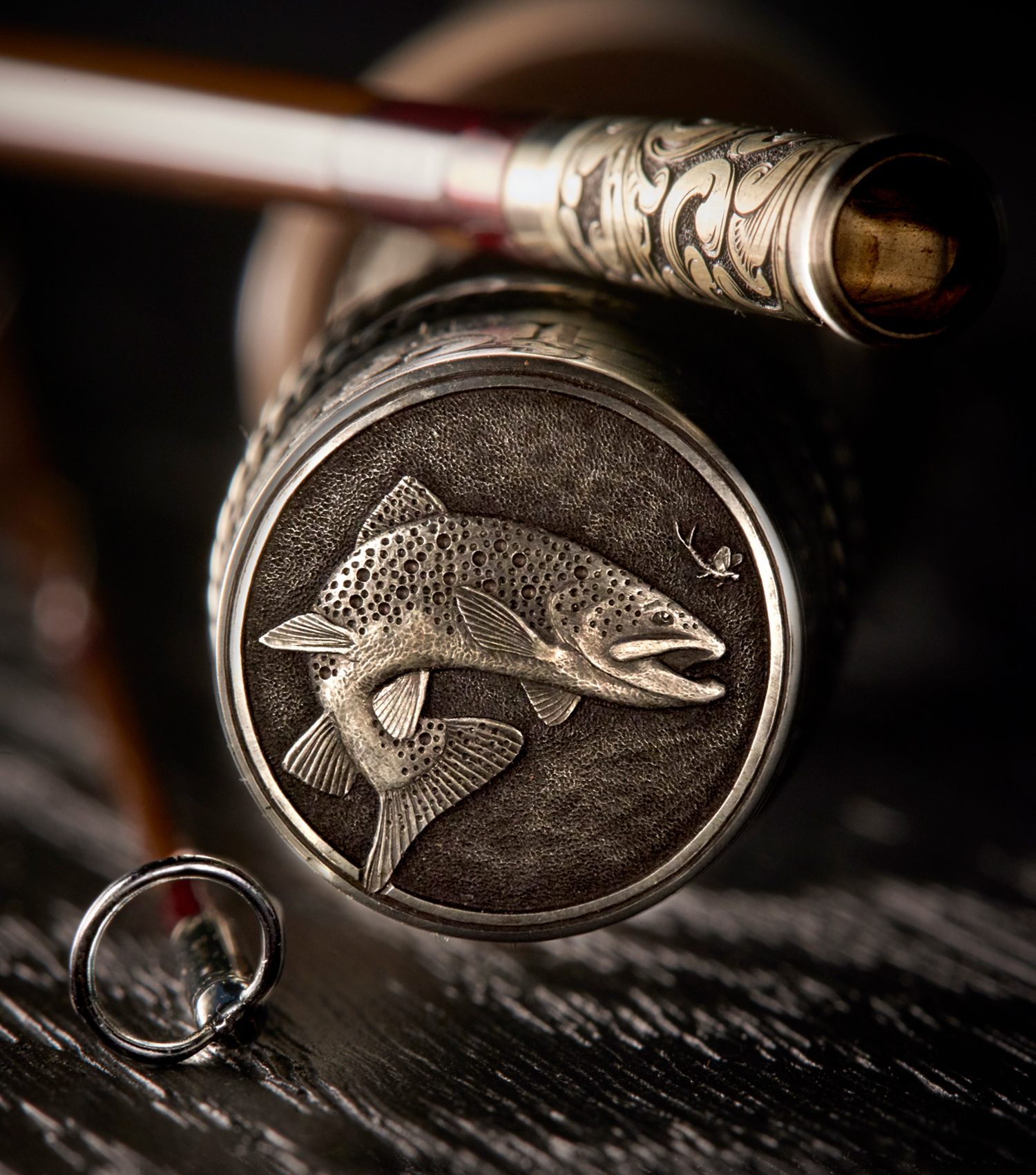 The end of a custom fly fishing rod from Bill Oyster engraved with a fish