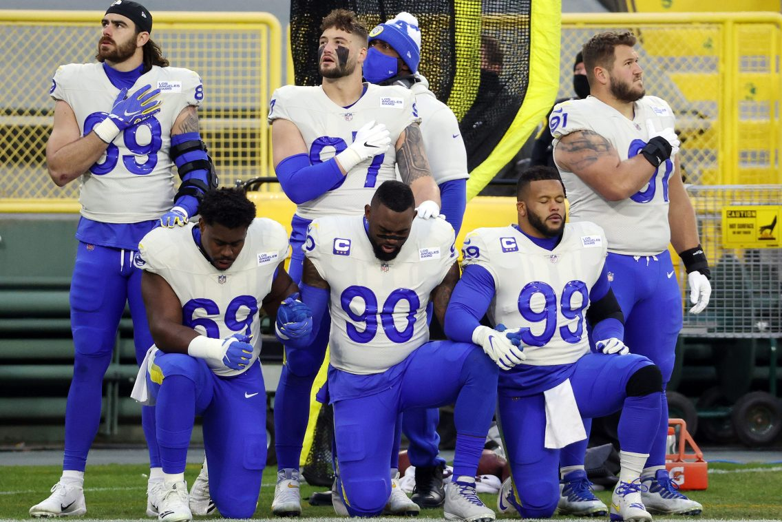 Members of the Los Angeles Rams kneel during the national anthem