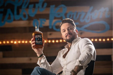 Fistful of Bourbon brand ambassador Anthony Bohlinger with a bottle of his brand's whiskey