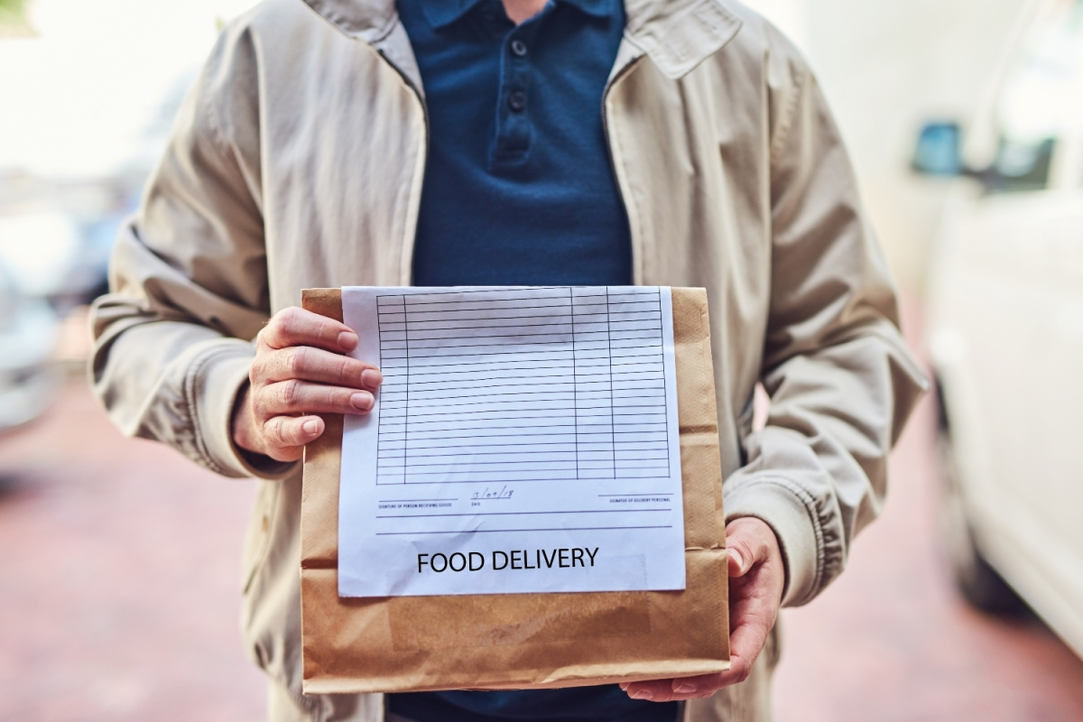 Food delivery man holding paper bag
