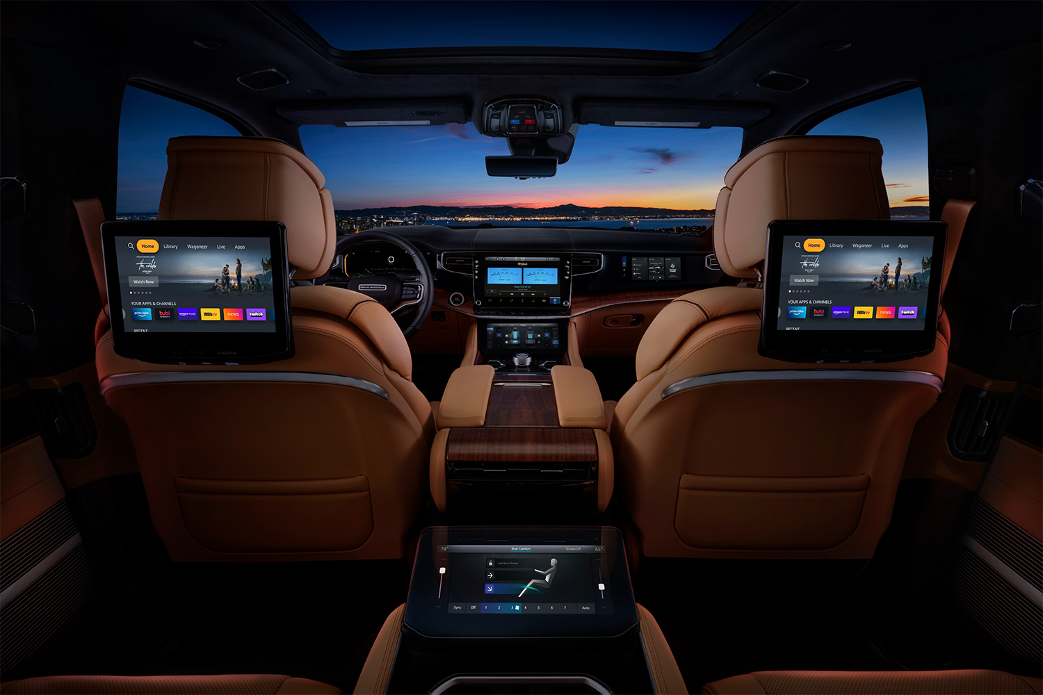 The interior of the 2022 Jeep Grand Wagoneer SUV shot from the second row, showing TV screens with Amazon Fire TV for Auto