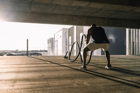 A man doing a HIIT workout by swinging battle ropes up and down