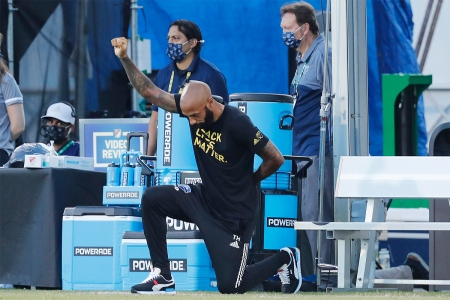 Thierry Henry, then head coach of the Montreal Impact, takes a knee at a match in July 2020