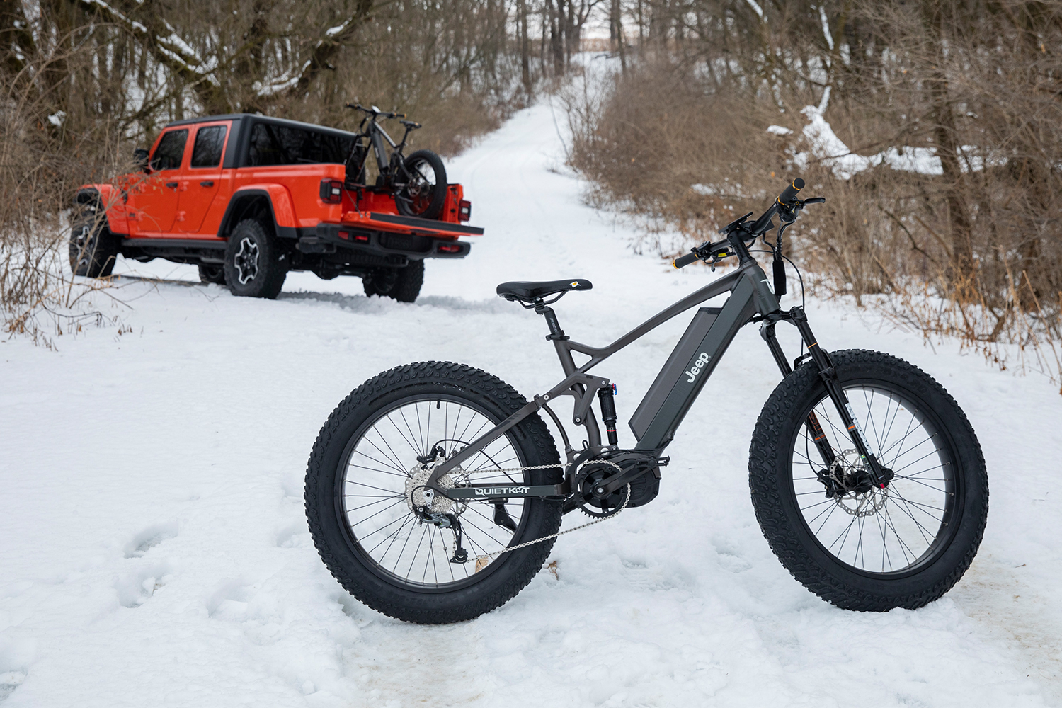 A Jeep e-bike sitting in the snow with an orange Gladiator pickup truck in the background