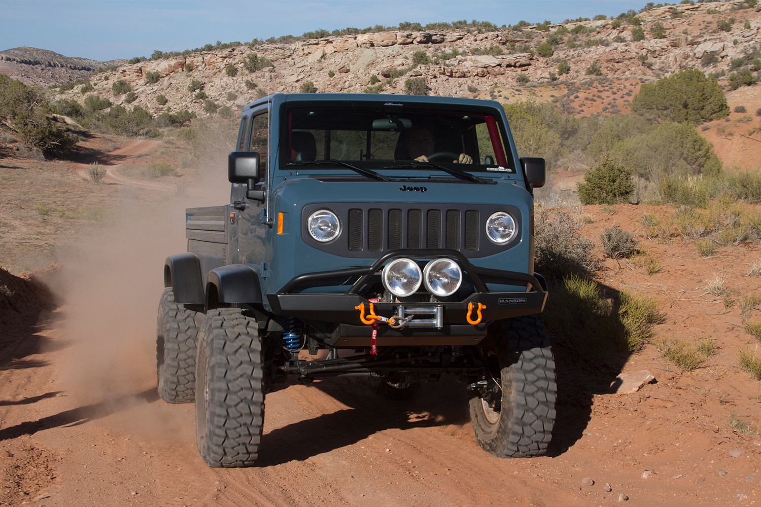 The Jeep Mighty FC cab-over-engine pickup truck driving in Moab