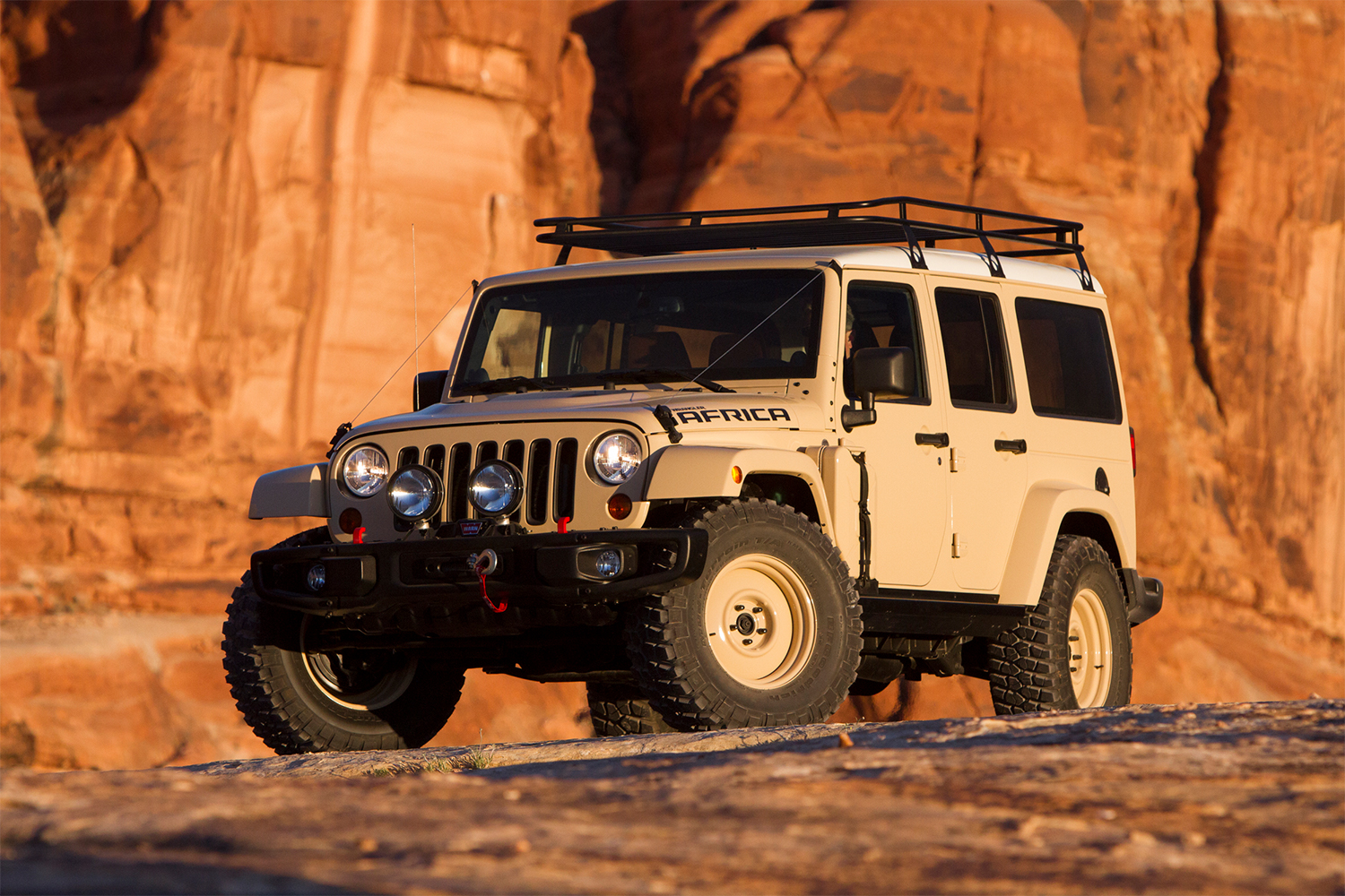 A tan Jeep Wrangler sitting on a cliff in Moab at the Easter Jeep Safari