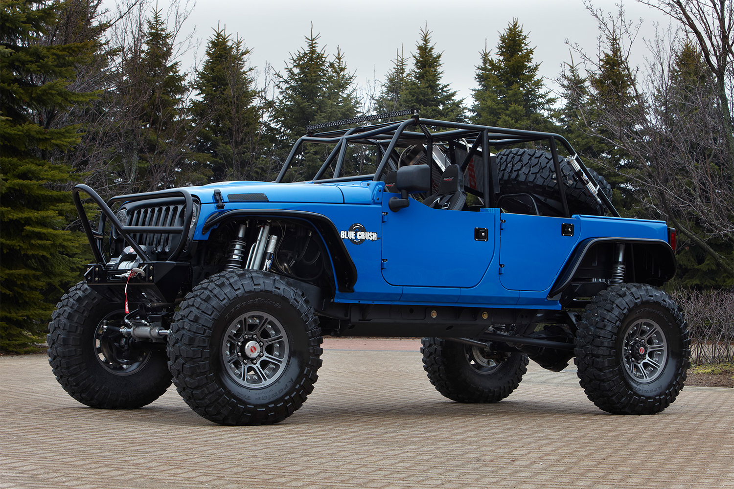 A blue Jeep Wrangler with a suspension lift and no roof
