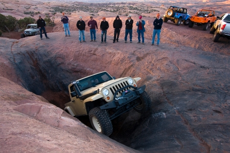 A beige Jeep Wrangler JT truck navigating an obstacle in Moah