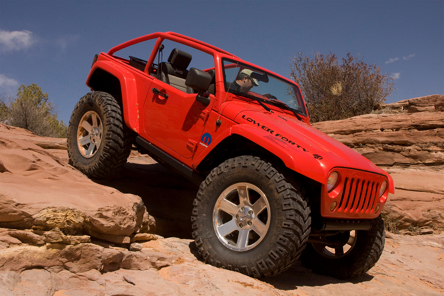 A red Jeep Wrangler with huge tires rock crawling at the Easter Jeep Safari
