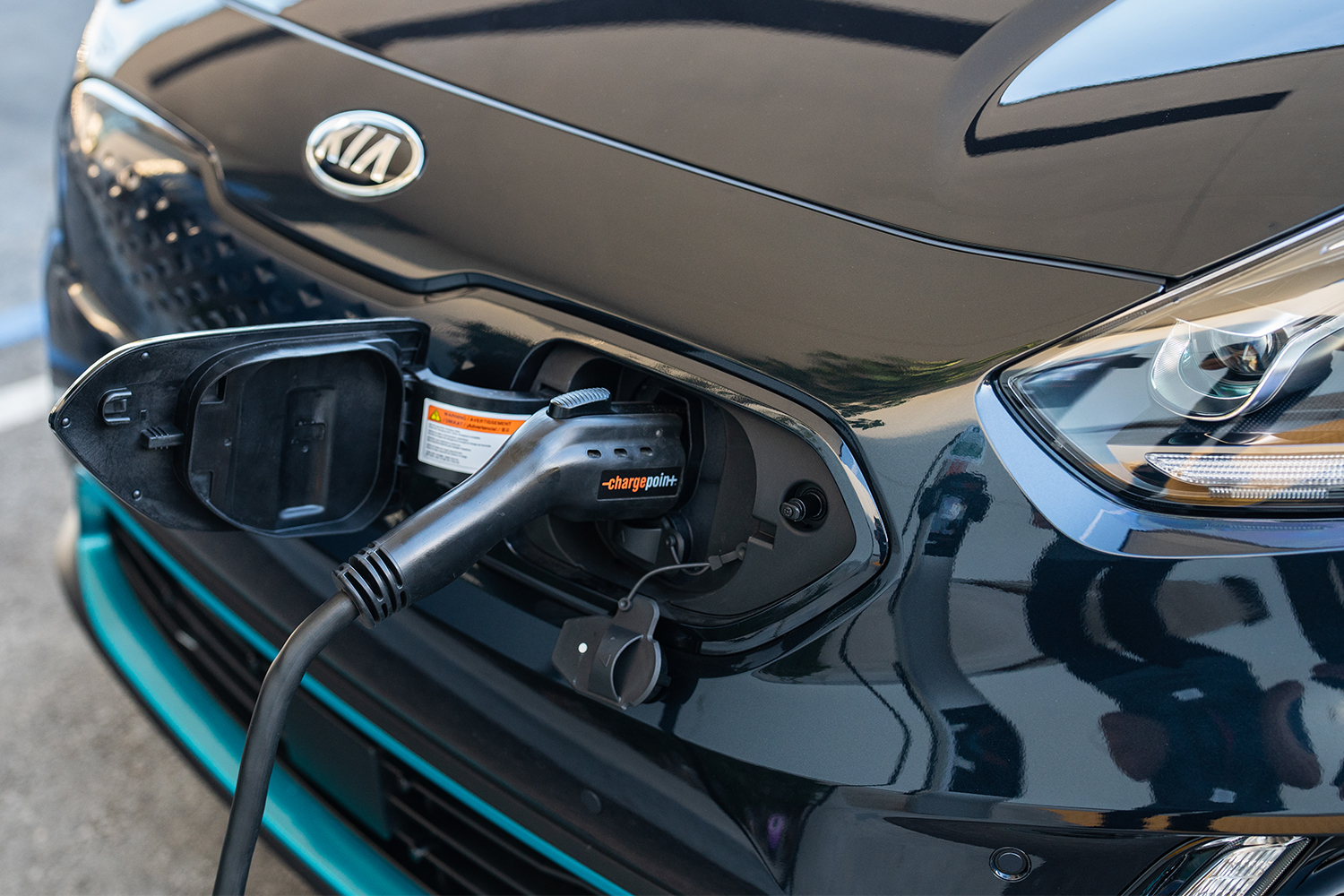 A ChargePoint electric car charger plugged into the front of the Kia Niro EV crossover