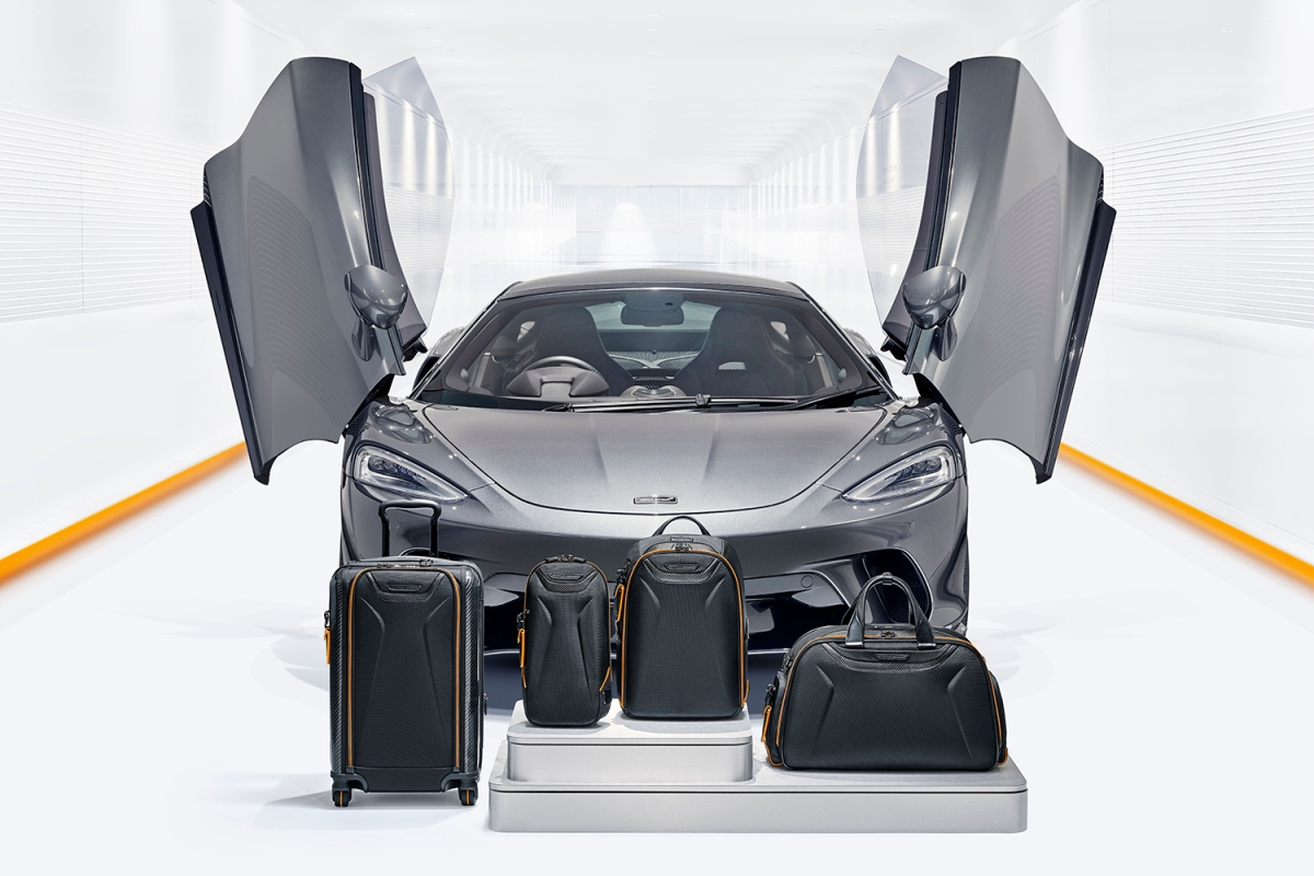 Four new TUMI bags with a McLaren supercar behind them